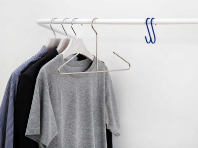 white cloth rail in large with t shirts and clothes hangers